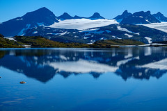Galdhøpiggen Reflections (Norway) (briburt) Tags: briburt fujifilm xe1 xf1855 panorama mountains glacier jotunheimen sognefjellshytta fantesteinsvatnet jotunheimennationalpark galdhøpiggen sun water glacial summer light stark norway norwegian blue glow sky azure landscape dramatic contrast majestic relaxing still quiet nature lake vatnet zen serene serenity