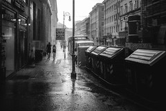 Walking in the rain in Trieste (Dannis van der Heiden) Tags: trieste rain corsoitalia catsanddogs garbagecontainer road bus people walking streetlight building sky shop couple nikond750 d750 tokina1628mmf28 soaked raining raindrops urban city monochrome blackandwhite