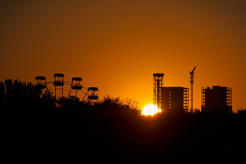 Sunset Over Ferris Wheel And Two Unfinished Buildings
