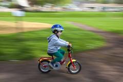 Vooooosh! (Christian Hacker) Tags: bicycle child bike ridingabike crediton park panning movement canon eos50d tamron 1750mm helmet howtorideabike boy vooosh grass pedals redbike infocus achievement cycling puky son