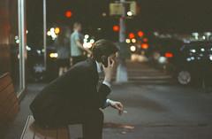 Ektachrome nightcrawlers 10: making sure she knows he quit (NYC Macroscopist) Tags: bokeh lowlight lowiso night late ektachrome midtown newyork nyc smoking guy man suit vintage leica summilux film analogue