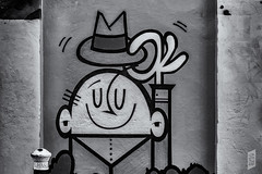 A tip of the hat to you. (Corbicus Maximus) Tags: streetart character southseaghetto ghetto southsea spray paint spraypaint spraycan graffiti monochrome blackandwhite hat man mural painting wall hand ears smile smiling nikon d7200 35mm lightroom niksilverefexpro2