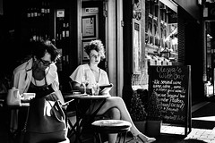 Alesya's introspection (Kieron Ellis) Tags: woman women book reading thinking introspection table drink wine stool glasses sign bag street candid blackandwhite blackwhite monochrome reflection window