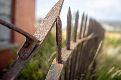 Rust (Howie Mudge LRPS BPE1*) Tags: rust rusty fence spike post bokeh bokehlicious bokehful abstract outside outdoors worn wornout old bend bent wall grass sony sonya7ii sonyalpha sonyalphagang 7artisans35mmf2 primelens sonyilce7m2