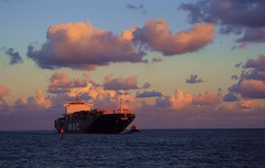 Freighter Arrival (PelicanPete) Tags: sky boat sea sunset water ocean freighter porteverglades florida mscmaureen arrival nature beauty natural colors colorful purple clouds cloudscape oceanscape seascape artisticsunsetphotography sunsetlight tugboat channel deep bow rocks boulders point fortlauderdaleflorida unitedstates usa harbourisles seaport 900ftlong 120feetwide shipportentranceseries