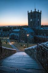 Blue Hour at St David's (SydPix) Tags: stdavids cathedral church pembroke pembrokeshire wales stone steps churchyard graveyard dusk sunset afterglow clock lamplight sydyoung sydpix