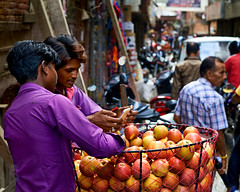 Two Nepali men discus what they are seeing on a smart phone in Kathmandu, Nepal (BryonLippincott) Tags: nepal thamel asia asian centralasia kathmandu nepali street streetscene men two talking smartphone device apples basket selling vendor streetmarket fruit busy traffic crowded friends happy