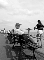 Contemplation (cngphotographic) Tags: hastings sea seaside seafront promenade man girls bench sunshine sunny water beach eastsussex shadows female woman girl shorts old street railings sky blackandwhite monochrome mono blanc et noir fujifilm hs50exr england uk britain sussex people crowd crowds holiday vacation outside outdoors candid cap