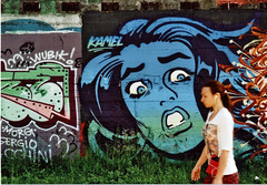 Oi! (fabio.mattutino) Tags: graffiti murales street art leitz 50mm afternoon parco dora torino turin italy color wall girl walking earphone cuffie maggio may 2018 analog whats up oi hey kamel paint