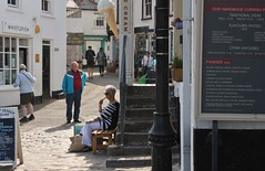 St Ives - May 2018 - Pipe Smoking Woman Candid (Gareth1953 All Right Now) Tags: stives street candid retired couple together almost waiting contemplating greyhair sunglasses sitting white trousers smoking pipe people seaside barefoot signs menus sit seated