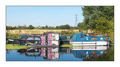 The River Dwellers (Sweet Toof), East London, England. (Joseph O'Malley64) Tags: theriverdwellers sweettoof streetartist streetart boatart urbanart publicart freeart graffiti boats boating homes dwellings abodes eastlondon eastend lonď england uk britain british greatbritain art artist artistry artwork mural muralist cruisers motorboats narrowboat riverboats canal canalised waterway marsh marshland floodplain walthamstowmarsh grassland naturereserve sssi siteofspecialscientificinterest londonplanetrees vegetation duckweed coots waterbirds wildlife pylon electricitypylon churchspire towercrane warehouse industrialestate water lackofaffordablehousing population overpopulated overpopulation urban urbanlandscape fujix fujix100t accuracyprecision