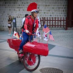 Strange Cyclist (Mondmann) Tags: deoksugung deoksupalace palace cyclist bicyclist bicycle bike costume flags nationalflags sidewalk streetstreetphotography street streetphotography seoul korea southkorea rok republicofkorea asia eastasia mondmann canonpowershotg7x