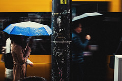 Amplified in the Silence (ewitsoe) Tags: canoneos6dii city rain street warszawa erikwitsoe summer urban warsaw wet water umbrella motion tram drive walking spring chilly readyforsomerain warm people man woman coats