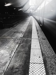 At the far end (LUMEN SCRIPT) Tags: france urbanphotography urban city paris fasttrain platform station transport shadow light backlight guidinglines vanishingpoint monochrome trainstation