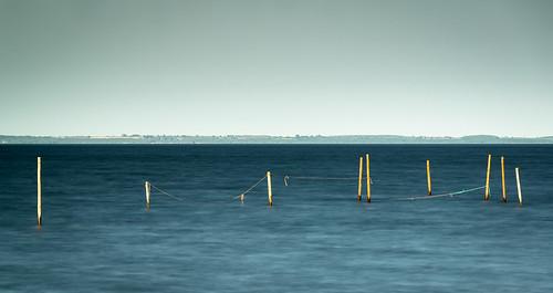 Pålar och fiskenät i sundet med Öland på andra sidan
