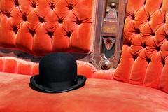 Gentleman Caller (Doris Burfind) Tags: sofa hat divan bowler blackandorange orange settee couch antique upholstered