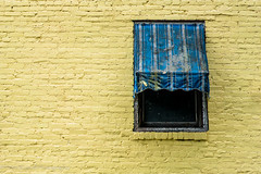 The Battered Awning (d_russell) Tags: sonya7rii sonnartfe1855za window awning yellow blue stripe brick glass building