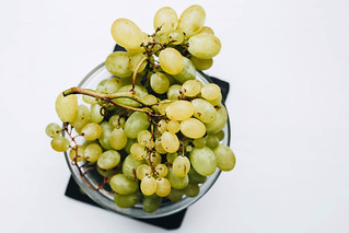 Top view of fresh grapes in a bowl on white background