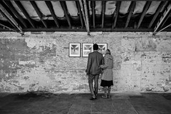 Appreciating Art 071 (Peter.Bartlett) Tags: noiretblanc art unitedkingdom people streetphotography olympuspenf westyorkshire woman candid peterbartlett man urban urbanarte monochrome uk m43 microfourthirds standing bw lunaphoto wall blackandwhite niksilverefex couple shipley england gb