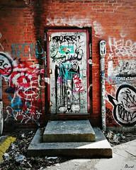 Kirkland Door (blamstur) Tags: graffiti colorful door alley sidelit brick paint