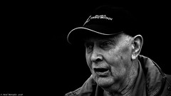Still impressive after all these years. (Neil. Moralee) Tags: middevonshow2018neilmoralee neilmoralee man old mature face portrait wrinkles cap great britain brunell bristol dockyard black white contrast blackandwhite mono blackbachground blackbackground dark surprised amazed amased hat hering aid hearingaid deaf deafness neil moralee nikon d7200 uk england close bw bandw