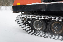 Caterpillar tracks of vintage snow groomer kicking up snow and g (blurMEDIA Stock) Tags: canada ontario quebec active adventure antique cabin caterpillartracks cold cottage driver driving f2 forest forestroad frozen fun holiday lifestyle machinery motion muskoka nature orange outdoor outdoors path recreation road rugged seasonal ski skiresort skiing snow snowgroomer snowstorm snowtires snowflake snowing snowy transportation travel vacation vehicle vintage wheel winter