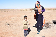 An Offer of Bread (meg21210) Tags: morocco berber berbere woman people child desert nomads nomad boy mother sahara oven bread cooking baking