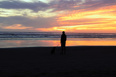 Watching the Sunset (twahl8) Tags: sun sand beach water waves sunset dog people oregon