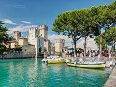Postcard from Italy (Karsten Gieselmann) Tags: 1240mmf28 blau burg em5markii europa exposurefusion farbe gardasee grün italy jahreszeiten lagodigarda lakegarda mzuiko microfourthirds olympus reise schiff seeteichweiher sommer sonne türkis wasserfahrzeuge wetter wolken blue castle clouds color green kgiesel lake m43 mft pond seasons summer sun travel turquoise weather sirmione lombardia italien