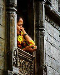 A woman looking out a window and smiling  at the Shree Pashupatinath Temple, Kathmandu, Nepal (BryonLippincott) Tags: nepal asia asian centralasia pashupatinath kathmandu nepalese nepali southernasia outside outdoors day daytime travel destination old ancient oriental building temple architecture exterior facade traditional culture heritage history historic hindu hinduism religious religion placeofworship sacred faith tourism touristattraction people group ceremony burial gather fire smoke pashupatinathtemple water river woman