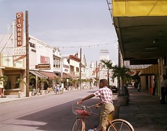 Looking north at the west side of Duval St. in Key West (State Library and Archives of Florida) Tags: florida keywest duvalstreet commercialbuildings businesses sidewalks children bicycles hotellaconcha