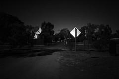 Signs and Signals (ChrisRSouthland) Tags: bw blackandwhite monochrome schwarzweiss dark sign satellitedish road leicammonochrom leicaelmarit28mmf28 australia alicesprings