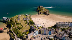 Aerial drone view of colorful buildings next to the ocean in a picturesque seaside town (Tenby, Wales, UK) (WhitcombeRD) Tags: ancient welsh sunny sand high bay tourist boats destination holiday sea above drone uk coastal architecture aerialview pembrokeshire view visit house town sandy water south tenby landmark side top old vacation beach picturesque tourism resort wales blue coastline beautiful britain travel summer british history aerial seascape tide coast harbour seaside