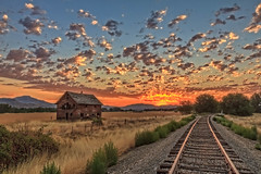 Beautiful Sunrise Over Old Homestead (http://fineartamerica.com/profiles/robert-bales.ht) Tags: facebook photouploads barn sunrise sunset house farm homestead ranch cattle barnwood fence butte squawbutte mountain idado landscape emmett idaho treasurevalley gemcounty scenicbiway americaphotography valley idahophotography beautiful sensational spectacular magnificent surreal sublime magical spiritual inspiring inspirational canonshooter haybales scenic wow stupendous superb building grass hay trees yellow blue robertbales sky railroad tracks