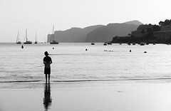 The fisherboy (Westhamwolf) Tags: boy fishing black white bw sea beach rod sand mountains boats majorca spain mallorca balearic island