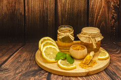 Golden honey in a jars, lemon slices, turmeric powder and lemon leaves on wooden plate on wooden background (zaklina.miljkovic) Tags: aroma aromatherapy background closeup color condiment curcuma delicious dessert dipper flavor food fresh glass gold golden green healthy herb home honey ingredient jar leaves lemon liquid medicine natural nutrition organic plate pot powder product products slices spice spoon sticks sweet texture turmeric wood wooden yellow