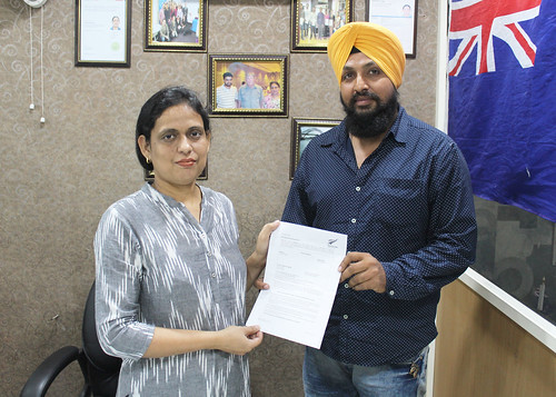Ms. Parwinder Kaur (Director of West Highlander) handing over New Zealand Dependent Visa to Arvinder Singh