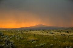 Stormy Evening (wyojones) Tags: wyoming parkcounty cody oregonbasinturnoff us14 greybullhighway sagebrush storm sun sunset grass clouds cloudscape rain heartmountain absarokamountains fence wyojones np