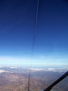 Jet contrails and shadow over California snow capped mountains