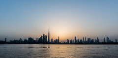 Panoramic view of Dowtown Dubai during a sunset, UAE (DavidGabis) Tags: yellow watercanal black high east sailing bay abstract city urban panorama emirates orange estate lights office uae travel panoramic town towers tourism profile tall architecture day sunrise business sun downtown view night skyline sky landscape sunset scene outdoor dubai dhow buildings cityscape modern line middle horizontal landmark exterior blue skyscraper silhouette beautiful futuristic hotel house asia design background arabic coast arab burjkhalifa