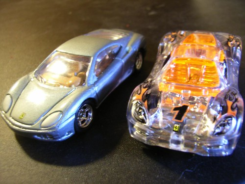 Two Hot Wheels Ferrari 360 Modena cars, one solid, one transparent.