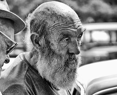 The whisper. (Neil. Moralee) Tags: neilmoralee steamrally2018neilmoralee man old mature beard grandad grandpa father bald whisper pair two men wrinkles craggy haggard gaunt worn life hard secret talk talking suffering anxiety wild face portrait candid norton fitzwarren uk facial hair wise wisdom networking fear suspicion deceit deceiving trust black white bw bandw blackandwhite olympus omd em5 neil moralee boiled sunshine people outdoor sneaky memmory deafness deaf