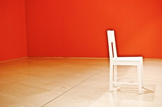 A solitaire white chair in a room with red walls