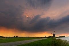 Summer Rain Shower (Johan Konz) Tags: rain shower dark cloud orange sunset sky mill silhouette landscape outdoor neck netherlands nikon d7500 road water canal grass field