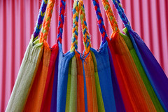 Colour and texture I (James_D_Images) Tags: colour fabric cloth braid hammock stripes yellow blue green orange red corrugated metal wall background abstract lines texture yarn thread