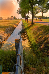 The Sun Is Burning Like Hell, Luckily The Ditches Don't Smell! (Alfred Grupstra) Tags: nature footpath outdoors grass ruralscene landscape tree scenics summer sunset autumn sky season nopeople sunlight beautyinnature fence greencolor tranquilscene nonurbanscene ditch road