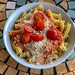 Top view of spaghetti with tomato sauce, grated cheese and fresh cherry tomatoes