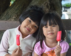 girls and popsicles (the foreign photographer - ฝรั่งถ่) Tags: two girls children friends sitting eating popsicles khlong thailand thanon portraits bangkhen bangkok nikon d3200
