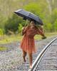 Rainy Day Fun (vtcollins) Tags: portrait fun break fashion photoshoot rainy day impromptu railroad tracks spring barefoot umbrella colorful green orange red dark