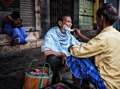 Early morning shave!  This man was having an early morning shave on the streets of Kolkata while his wife had a quick snooze in the background (Gerrykerr) Tags: street kolkata travel india ngc stphotographica